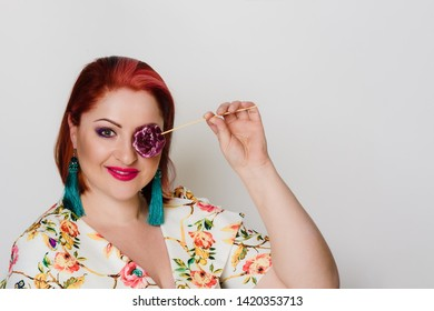 Portrait of happy smiling red-haired woman posing with lollypop