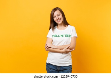 Portrait of happy smiling satisfied woman in white t-shirt with written inscription green title volunteer isolated on yellow background. Voluntary free assistance help, charity grace work concept