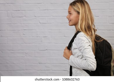 Portrait of happy smiling school girl wearing backpack. Good posture concept.