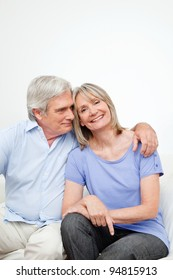 Portrait of happy smiling senior couple embracing at home