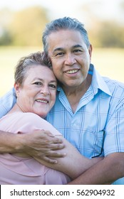 Portrait happy smiling senior hispanic couple relaxed hugging, embracing each other, showing love and affection, outdoor blurred background.