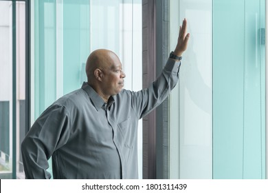Portrait of happy smiling senior old elderly business Black African American man person standing, touching, and looking at the window in meeting room in corporate office.