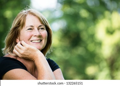 Portrait of happy smiling senior woman - outside on sunny day