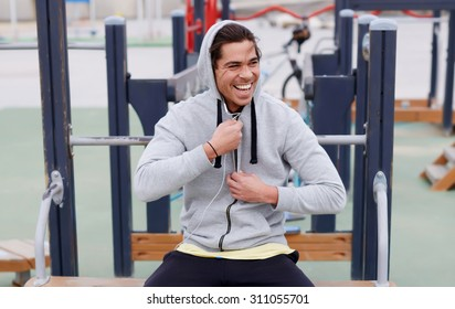 Portrait of a happy smiling sportsman having a break after workout outdoors, jogger man listening to music in headphones enjoying rest,young sporty guy resting after training sitting on sports ground