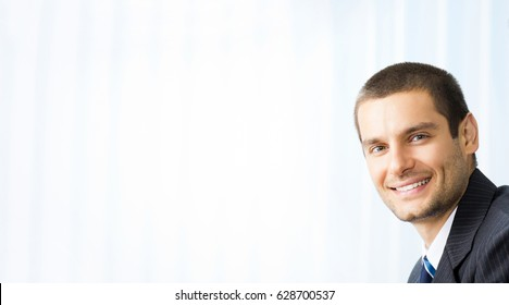 Portrait happy smiling successful businessman at office. Success in business concept. Blank copyspace area for slogan, advertisiment or text.