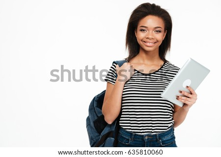 7871ee9926 Portrait of a happy smiling teen girl with backpack holding pc tablet and  looking at camera