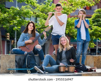 Portrait of happy smiling teenage band playing music together in park