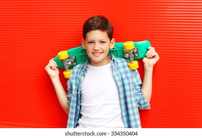 Portrait happy smiling teenager boy wearing a checkered shirt with skateboard in city over red background