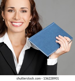Portrait of happy smiling thinking business woman with blue notepad or organizer, over gray background