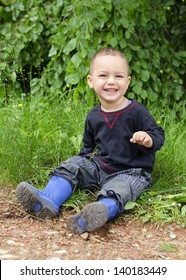 Portrait of a happy smiling toddler child sitting on a green grass in park.