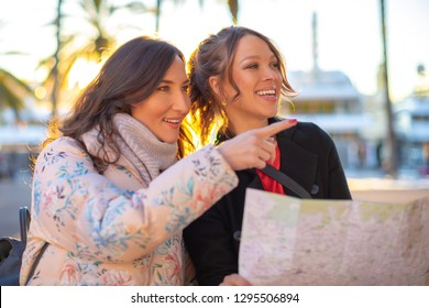 Portrait of happy smiling tourists looking at the map - two young beautiful women looking for the right way.
