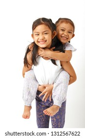 Portrait of a happy smiling two little sisters girls hugging on white background