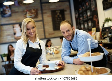 Portrait of happy smiling waiter and waitress in cafeteria elbowing on counter.