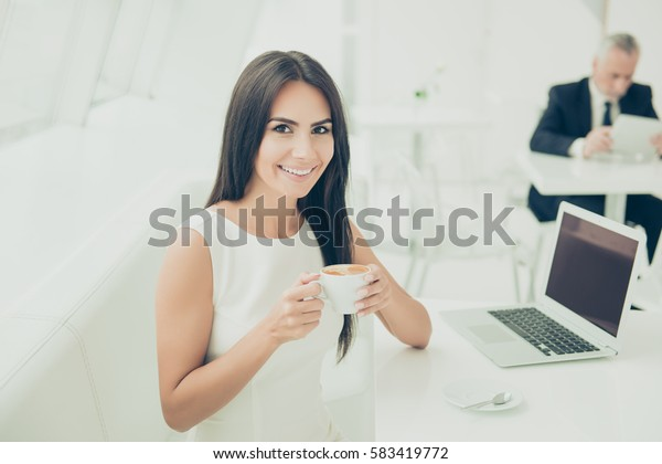 A portrait of happy smiling woman drinking a cup of hot coffee and sitting at the table with a laptop