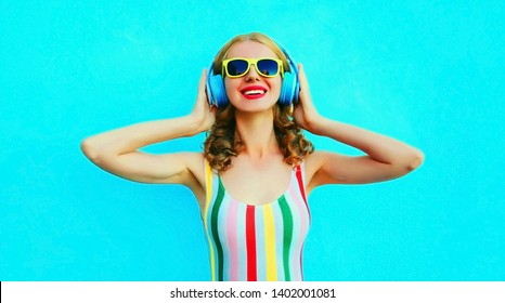 b60f2c7159 Portrait happy smiling woman listening to music in wireless headphones on  colorful blue background