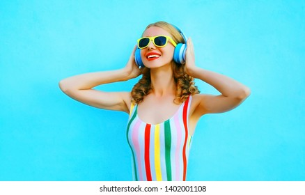 Portrait happy smiling woman listening to music in wireless headphones on colorful blue background