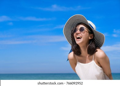 Portrait of happy smiling woman on the beach on a beautiful . Pretty girl asian in casual looking away and smile , laughing. The beach beautiful at bright sky