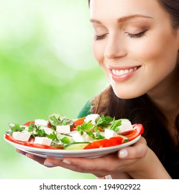 Portrait of happy smiling woman with plate of salad, outdoors