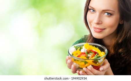 Portrait of happy smiling woman with plate of salad, outdoors, with blank area for copyspace
