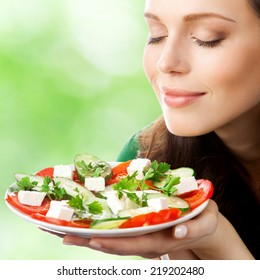 Portrait of happy smiling woman with plate of salad, outdoor