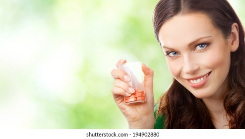 Portrait of happy smiling woman showing bottle with pills, outdoors, with blank area for copyspace
