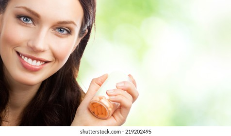 Portrait of happy smiling woman showing bottle with pills, outdoor, with blank area for copyspace
