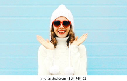 Portrait happy smiling woman surprised in heart shape sunglasses, knitted hat, sweater on blue background