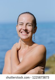 Portrait of happy smiling woman. Wet girl hides her nudity under her arms and posing smiling, squinting from the sun and looking at camera