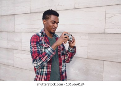Portrait happy smiling young african man with vintage film camera taking picture walking on city street over gray brick wall background