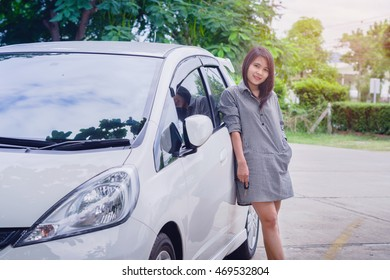 Portrait happy smiling young attractive woman standing next to new white car,Holding Car Keys