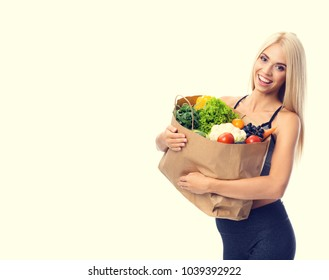 Portrait of happy smiling young beautiful woman in fitness wear, holding grocery shopping bag with healthy vegetarian food, with copyspace area for slogan or advertising text message, over yellow.