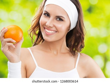 Portrait of happy smiling young beautiful woman in fitness wear with orange, outdoors