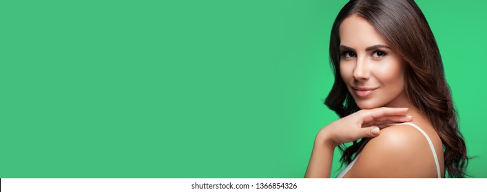 Portrait of happy smiling young beautiful woman in white casual clothing, over green background, with big copy space area, for some text, advertising or slogan
