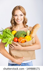 Portrait of happy smiling young beautiful woman holding grocery shopping bag with healthy vegetarian raw food, over gray background