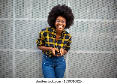 Portrait of happy smiling young black woman with afro hair holding mobile phone