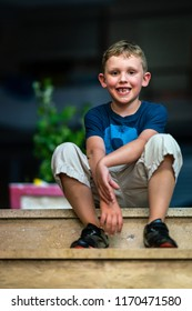 Portrait of a happy smiling young boy sitting on stone stairs outdoors at night.