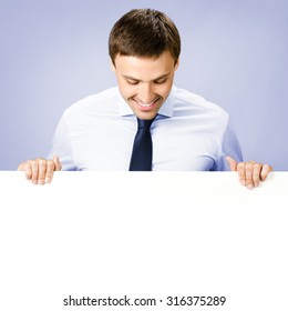 Portrait of happy smiling young business man showing blank signboard, over violet background