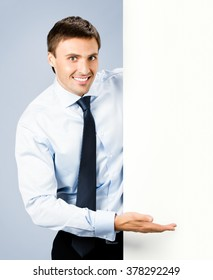 Portrait of happy smiling young business man showing blank signboard, over grey background