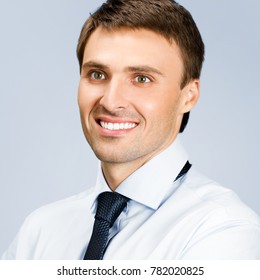 Portrait of happy smiling young business man, over grey background