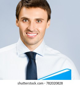 Portrait of happy smiling young business man with blue folder, over gray background