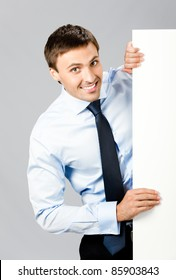 Portrait of happy smiling young business man showing blank signboard, over gray background