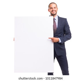 Portrait of happy smiling young businessman pointing to blank board