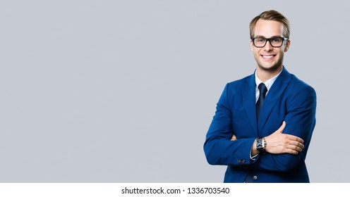 Portrait of happy smiling young businessman in glasses, over grey background. Business expert and success concept. Blank copy space area for advertisiment, slogan or text.