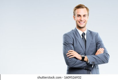 Portrait of happy smiling young businessman in grey confident suit, with copy space for some slogan or text. Business success concept.