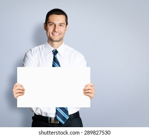Portrait of happy smiling young businessman showing signboard, against grey background. Copyspace blank area for slogan or text. Business and success concept.