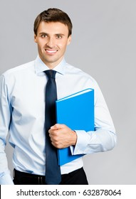 Portrait of happy smiling young businessman with blue folder, over grey background. Success in business concept.