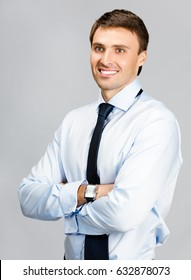 Portrait of happy smiling young businessman, over grey background. Success in business concept.