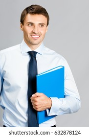 Portrait of happy smiling young businessman with blue folder, over gray background. Success in business concept.