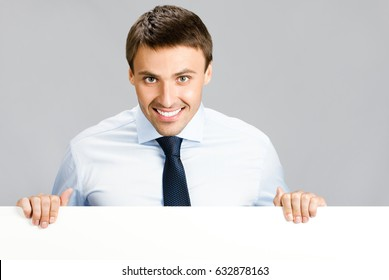 Portrait of happy smiling young businessman showing signboard, with blank copyspace area for slogan, advertisiment or text message, over grey background. Success in business concept studio shot.
