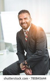 Portrait of happy smiling young businessman.He is sitting at a desk in his office.